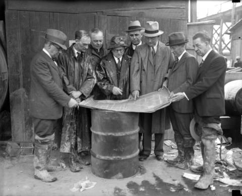 On April 15, 1931, investigators from the coroner's jury look over blueprints of the unfinished sanitary district tunnel where a fire killed eleven men on April 13, 1931. From left are James Versluis, city construction engineer; John Garcia, mining engineer; Elmer Stevens, State Street merchant; Coroner Herman Bundesen, Edward Kelly, chief engineer of the sanitary district; John Dean, assistant to the chief city construction engineer; John Pirie, president of Carson Pirie Scott  and Dr. Frederick Tonney, head of the city health research bureau.