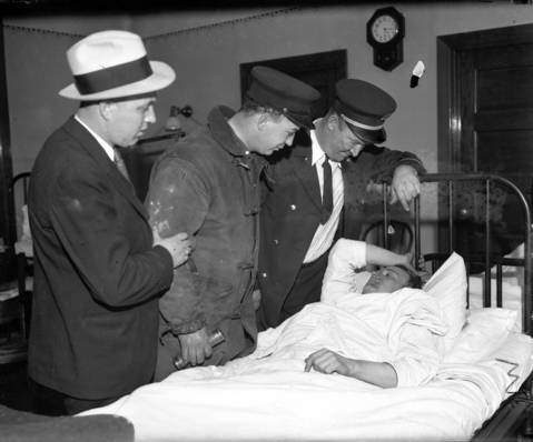 Firefighter William Fitzgerald is visited by John Mahoney, from left, John Fitzgerald (William's brother), and Capt. James Cotter of Squad A at St. Anthony's Hospital on April 14, 1931. Fitzgerald was one of the many firefighters that were injured while trying to save the laborers and other firefighters trapped in the sanitary district tunnel during the fire.