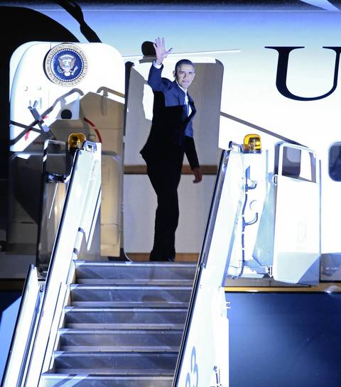 President Barack Obama waves as he enters Air Force One at O'Hare International Airport, in Chicago. The President was in town to attend fundraisers for the Democratic National Committee.
