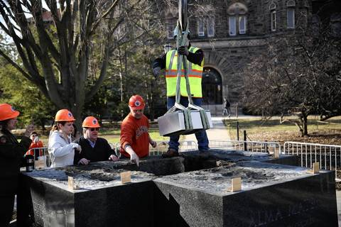 A time capsule is placed inside the base of the University of Illinois' Alma Mater sculpture before it is returned to campus after restoration work.