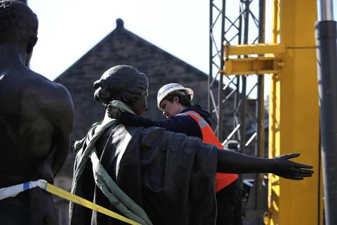 Peter Rybchenkov with Methods and Materials prepares the University of Illinois' Alma Mater sculpture to be lifted by a crane onto it's base as it is returned to campus after restoration work.