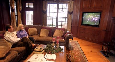 Steve Bisciotti watches a game with his wife Renee at his home in Millersville after becoming a minority owner of the Ravens.