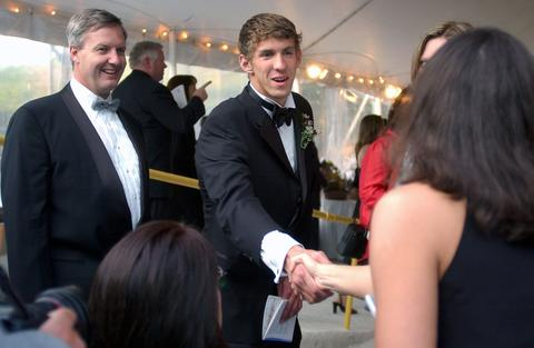 Michael Phelps greets Becky Galli during a black tie fundraiser for the North Baltimore Aquatic Club.