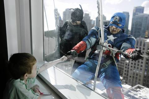 Dressed as Captain America, Roberto Duran, bumps fists with patient Zakk Carrier, 5.