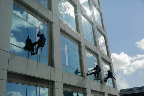 The three men move down the windows of the building.