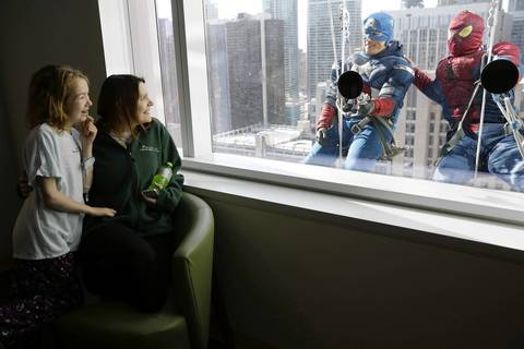 Patient Madison Houser, 12, and her mother Kristina Forest are entertained by Captain America and Spider-Man.
