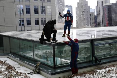 Window washers Pedro Castro, left, as Batman, Roberto Duran, center, as Captain America and Gerardo Vaca as Spider-Man wave to patients from the atrium roof after descending.