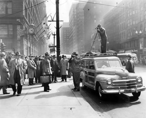 "WGN-TV newsreel photographers Fred Giese, on the curb, and Leonard Bartholomew, positioned on the car, shoot pictures in the Loop on March 22, 1948. This photo ran on April 4, 1948 with the announcement in the Tribune that WGN-TV would started its transmission the next day. Both Giese and Bartholomew were the first cameramen appointed to the eight man WGN-TV Newsreel staff. Bartholomew had been a veteran still photographer for the Tribune who earned the nickname ""the man who's late for dinner."""