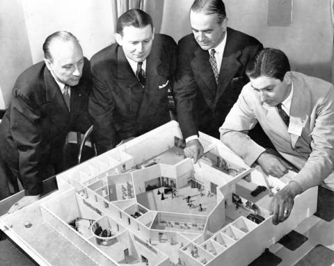 A model of the post-war television studio is viewed at the Palmer House by G. William Lang, from left, WGN chief engineer; Frank P. Schreiber, WGN general manager; P. C. McCabe of the Austin company which built the model; and J. D. McLean of General Electric company's television equipment division on Aug. 28, 1944.