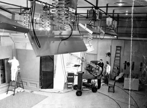 "A view of the floating television studio in WGN's building, in Tribune Square, which began operations on Jan. 25, 1950. The studio is 34 by 52 by 22 feet and floats on inflated rubber bags. Air space is provided between the walls and the ceiling and the building proper to eliminate outside noise and vibrations. The cameramen were filming ""Chicago Cooks with Barbara Barkley,"" one of televisions earliest homemakers."