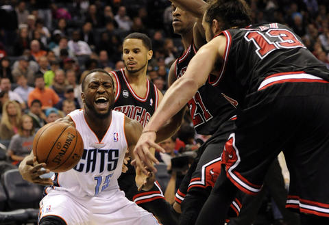 The Bobcats' Kemba Walker looks to pass as he is defended by the Bulls.