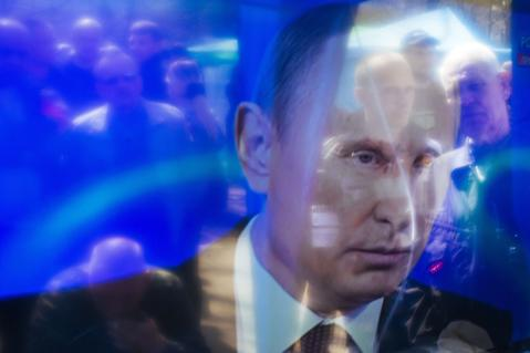 Pro-Russian activists are reflected on a TV screen as they watch a TV broadcast of Russian President Vladimir Putin's annual question-and-answer session on April 17. (Getty Images)