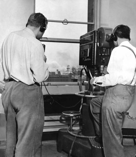 Spencer Allen of WGN-TV news room, left, and television cameraman William Rockar, right, televising the fire at North Pier Terminal Warehouse from the 6th floor of Tribune Tower on April 22, 1950.