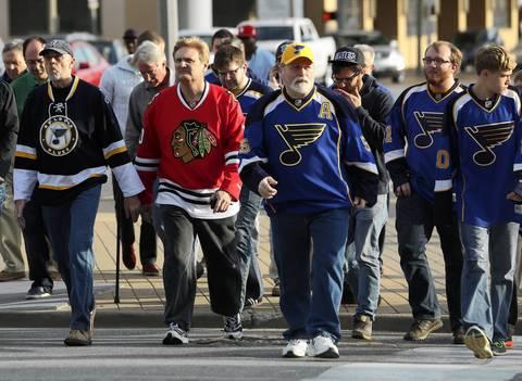 A Blackhawks fan crosses the street among Blues fans before Game 1 in St. Louis.