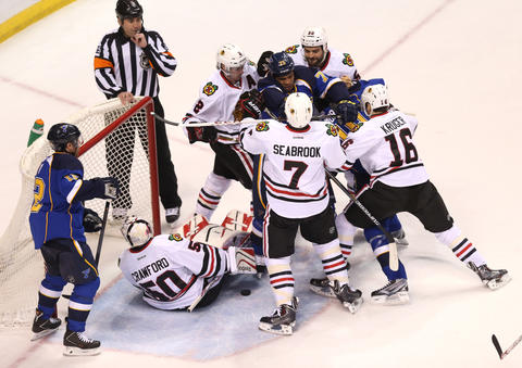 The Blues' Ryan Reaves is surrounded by Blackhawks during a fight in the first period.