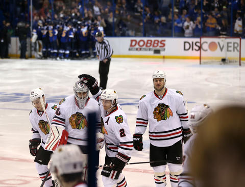 Blackhawks goalie Corey Crawford is consoled by Duncan Keith as the Blues celebrate their victory in triple overtime.