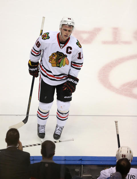 Jonathan Toews skates off the ice as blood drips down his face after a big hit against the Blues.