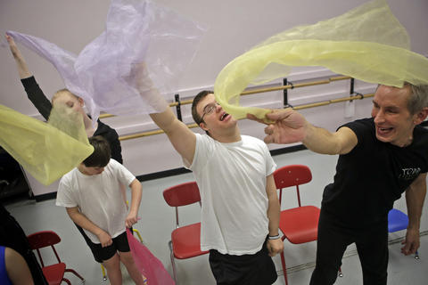 Jackson Koelling, center, and Todd Rosenlieb, right, smile as they wave scarves through the air during an adaptive dance class for children with Down syndrome at the TRDance Center in Norfolk. The class is taught by Rosenlieb and a physical therapist from CHKD participates. Several volunteers also assist the children as well.