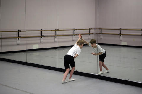 Gus Zaletski practices bowing in a mirror by himself after an adaptive dance class for children with Down syndrome at the TRDance Center in Norfolk. The class is taught by Todd Rosenlieb and a physical therapist from CHKD participates. Several volunteers also assist the children as well.