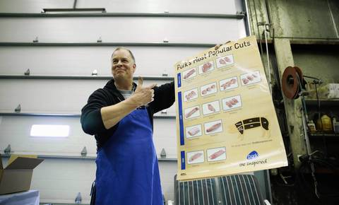 Tom Ulrich displays a chart of various pork cuts.