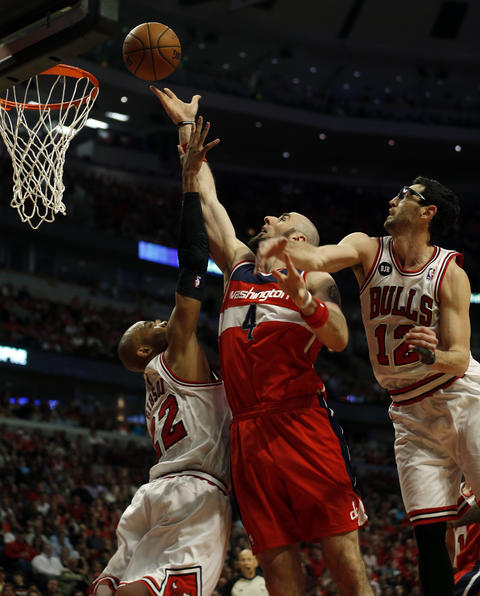 The Wizards' Marcin Gortat scores between Taj Gibson and Kirk Hinrich in the 4th quarter.