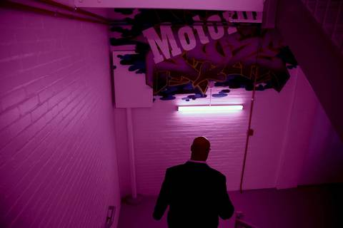 A man heads down a stairwell which is bathed in purple light.
