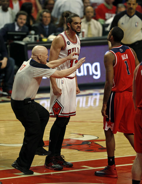 Joakim Noah and the Wizards' Trevor Ariza have words as official Joey Crawford moves in during the third quarter.