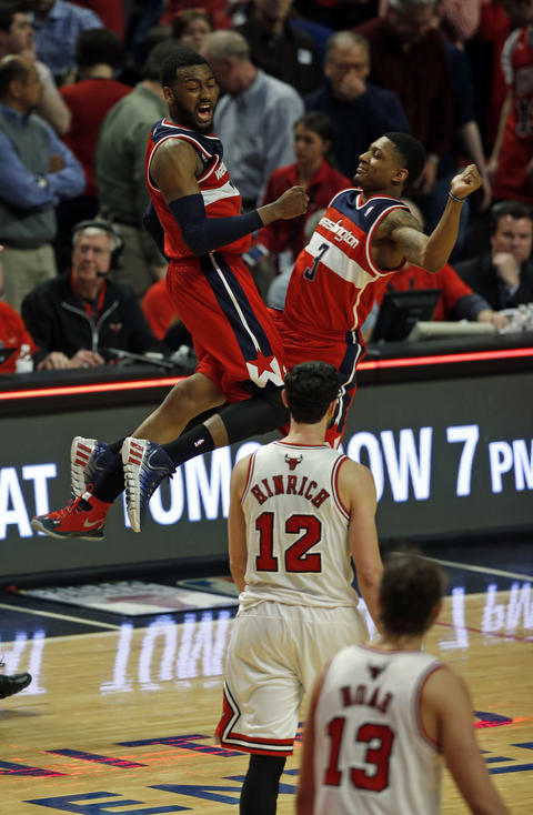 Kirk Hinrich walks away as the Wizards' John Wall and Bradley Beal celebrate their 101-99 win in overtime.
