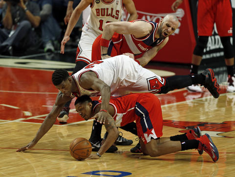 Jimmy Butler and the Wizards' Bradley Beal vie for a loose ball in front of Marcin Gortat in the 4th quarter.