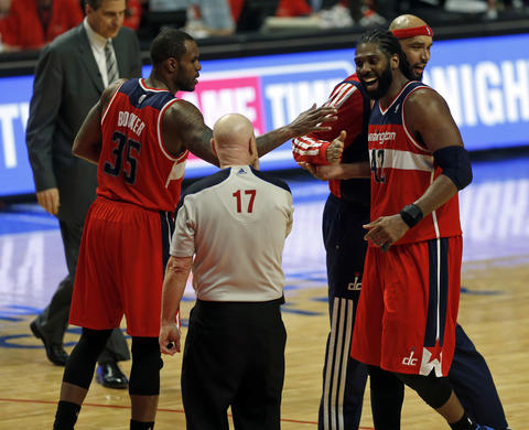 The Wizards' Nene smiles at official Joe Crawford while being congratulated by Trevor Booker and Drew Gooden during the 4th quarter.
