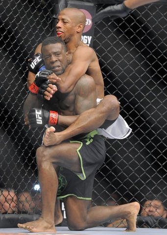 Chris Beal (green trunks) is held by Patrick Williams (white trunks) during UFC 172.