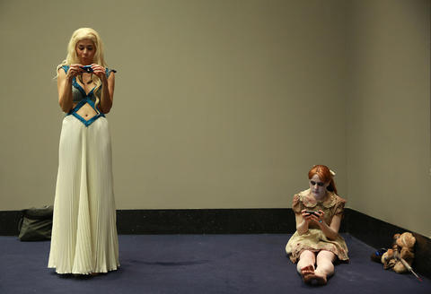 """Kathleen O'Brien, dressed as """"Game of Thrones"""" character Daenerys Targaryen, left, looks at her camera as Katelyn Redinger, dressed as Bioshock video game character Little Sister, uses her phone during the C2E2 Championships of Cosplay preliminary judging at McCormick Place on Saturday."""