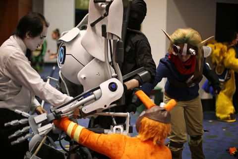 """Brian Beech, dressed as """"Portal 2"""" video game character Atlas, is helped with his costume during the C2E2 Championships of Cosplay preliminary judging at McCormick Place on Saturday."""