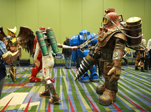 """Malinda Mathis, left, leads her husband Kyle, dressed as """"Bioshock"""" video game character Big Daddy, through the waiting room during the C2E2 Championships of Cosplay preliminary judging at McCormick Place on Saturday."""