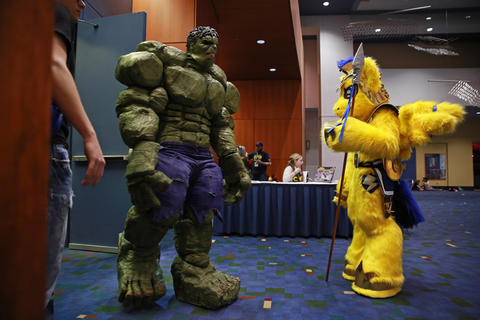"""John Quade, dressed as the Incredible Hulk, left, exits the judging room as Steve Schertz, dressed as """"My Little Pony"""" character Flash Sentry, waits to enter during the C2E2 Championships of Cosplay preliminary judging at McCormick Place on Saturday."""
