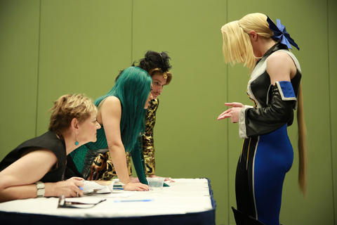 Judges Nan Cibula-Jenkins, from left, Yaya Han, and Austin Scarlett look over the details of Noelle d'Arda's costume during the C2E2 Championships of Cosplay preliminary judging at McCormick Place on Saturday.