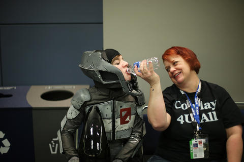 """Courtney Murphy, dressed as """"Borderlands 2"""" video game character Zer0, gets a drink of water with help from her mother Wendy before the C2E2 Championships of Cosplay judging at McCormick Place on Saturday."""