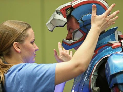 Trevor Walmer, dressed as a character named Iron Patriot, gets help with his helmet from Chrystine Shelton before the C2E2 Championships of Cosplay judging at McCormick Place on Saturday.