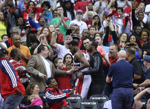 The Wizards' John Wall ends up in the stands chasing a loose ball in the fourth quarter.