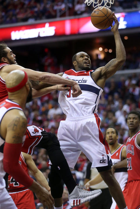 The Wizards' Trevor Booker goes to the basket against Joakim Noah.