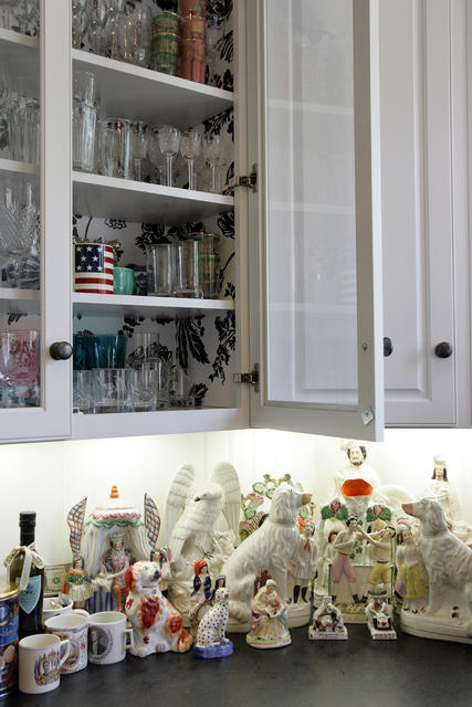In the Hancock Park kitchen of Johnson Hartig, co-designer of clothing line Libertine, Hartig taped up damask wrapping paper from Soolip in the glass-front cabinets. Under-cabinet lighting shows off Hartig's diverse collection of ceramics.