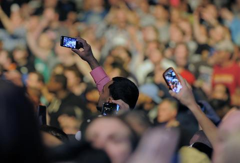 Fans take photos as Jon Jones battles Glover Teixeira.