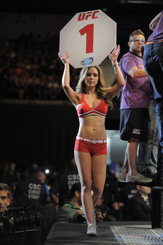 A ring girl carries the Round 1 sign.