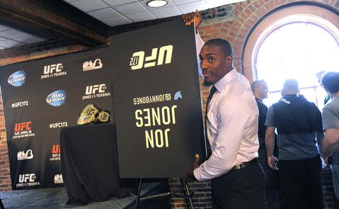 Phil Davis flips over Jon Jones' placard at the UFC's media event at Camden Yards.