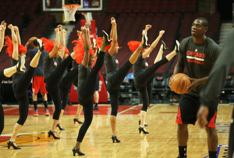 Bulls cheerleaders warm up as Ronnie Brewer takes practice shots.