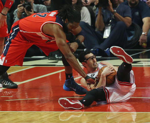 Kirk Hinrich falls to the floor while reaching for a rebound as the Wizards' Nene defends in the first quarter.