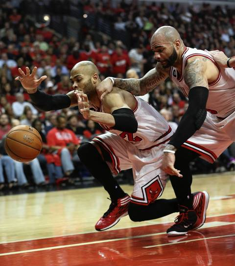 Taj Gibson and Carlos Boozer try to save a ball from going out of bounds in the first half.