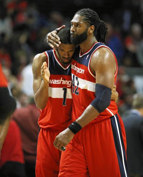 The Wizards' Trevor Ariza and Nene hug each other in the final seconds.