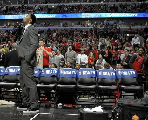 Derrick Rose stands on the sideline during a second half.