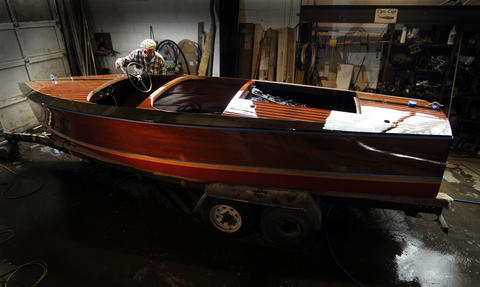 John Carl, a master woodworker, applies the ninth coat of marine varnish to a 1942 17' Chris Craft special mahogany runabout.